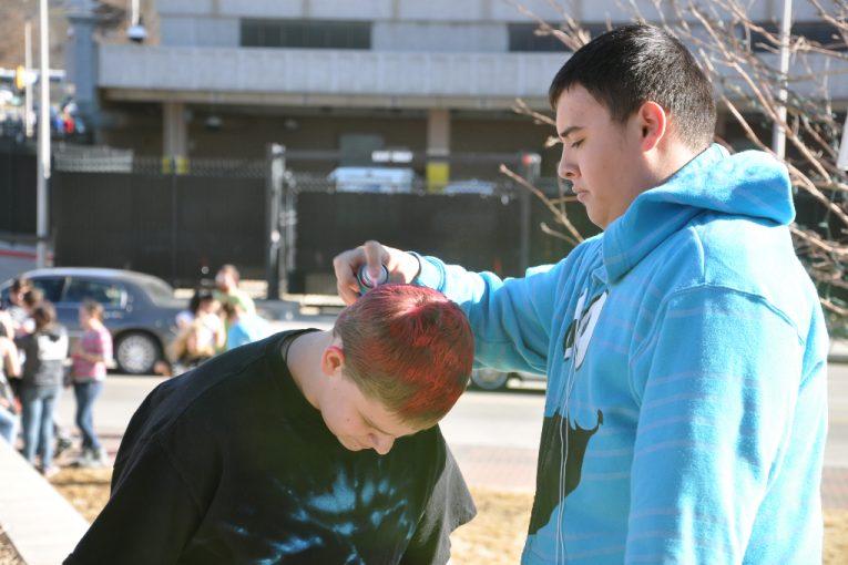 spraying his friends hair