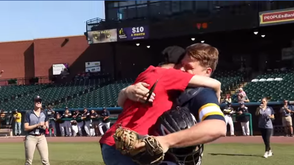 Marine surprises his mom when she throws the first pitch!